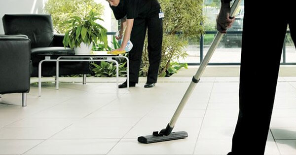 Woman Cleaning While Man Vacuums