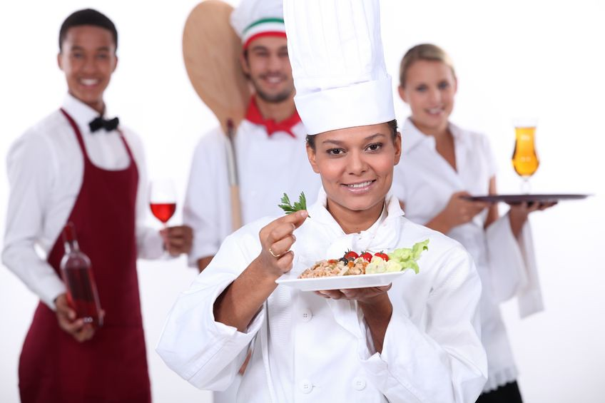Lady Chef in Uniform Presenting Food with chefs behind her