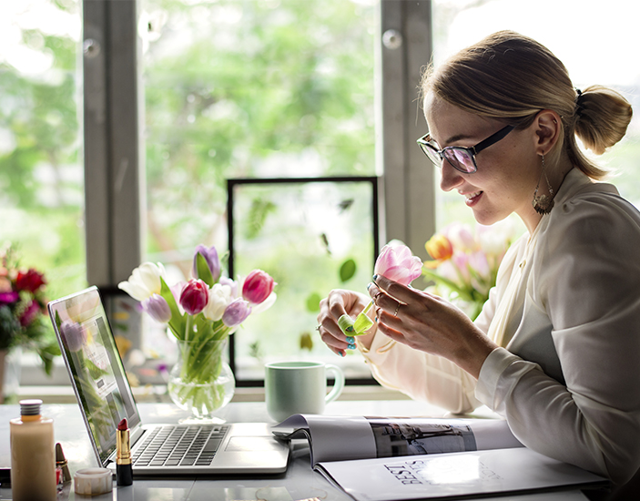 Smiling lady with laptop open looking at plant