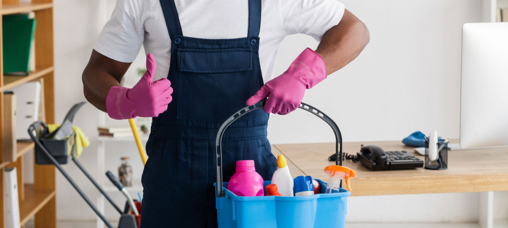 Person holding a bucket with cleaning supplies
